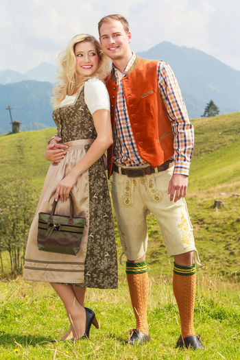 Bavarian couple in love posing on a meadow in the mountains. Bavarian Casual Clothing Day Dirndl Feelings Folk Clothing Folklore Full Length Grass Happiness Leather Pants Leisure Activity Lifestyles Men Mountain Outdoors Real People Smiling Standing Togetherness Two People Women Young Adult Young Men Young Women