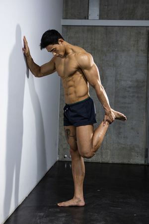 Male fitness model stretching by pushing up against a wall. Full body shot. Adult Asian  Athlete Body & Fitness Excersing Human Body Man Nam Vo Profile Shirtless Sportsman Wall Fitness Model Grey Wall Handsome Hunk Male Muscle Muscular Build One Person Shorts Stretching Strong Studio Shot Torso