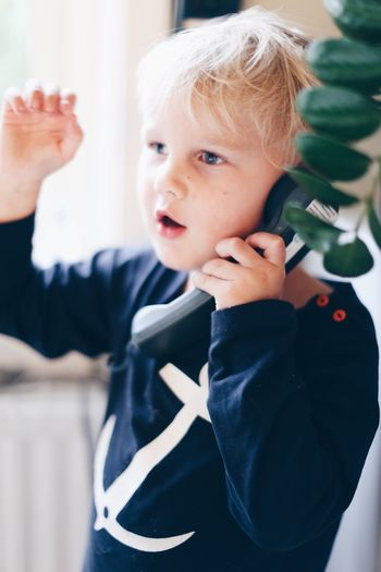 Close-up of cute boy talking on telephone at home