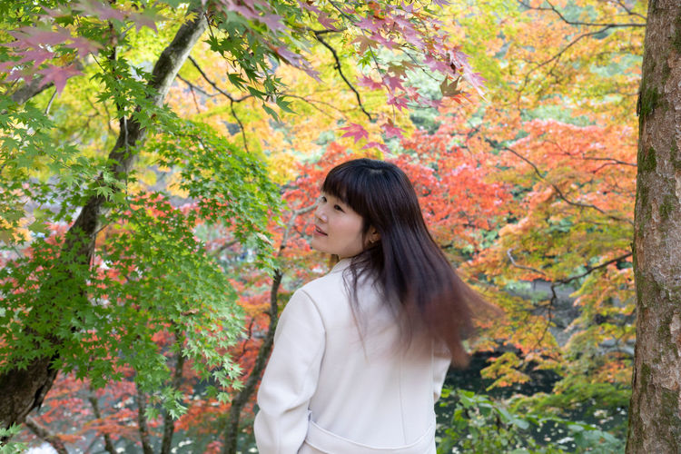 Beautiful young woman standing by trees during autumn
