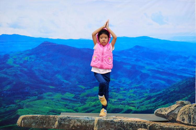Portrait of girl doing yoga on rock against mountains