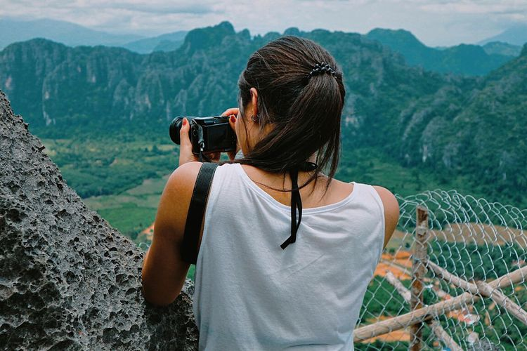 Rear view of woman photographing nature against mountains