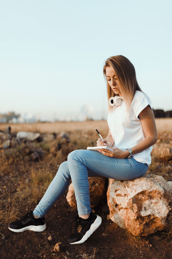 Young woman writing on diary while sitting on rock at farm