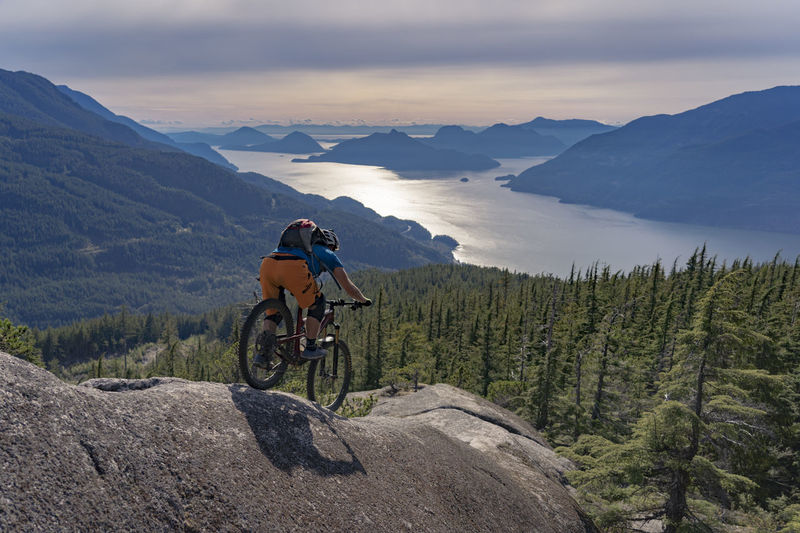 Rear view of man riding bicycle on mountain