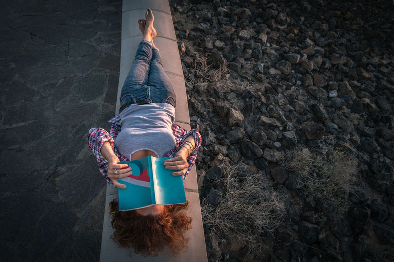 High angle view of woman with book lying on retaining wall