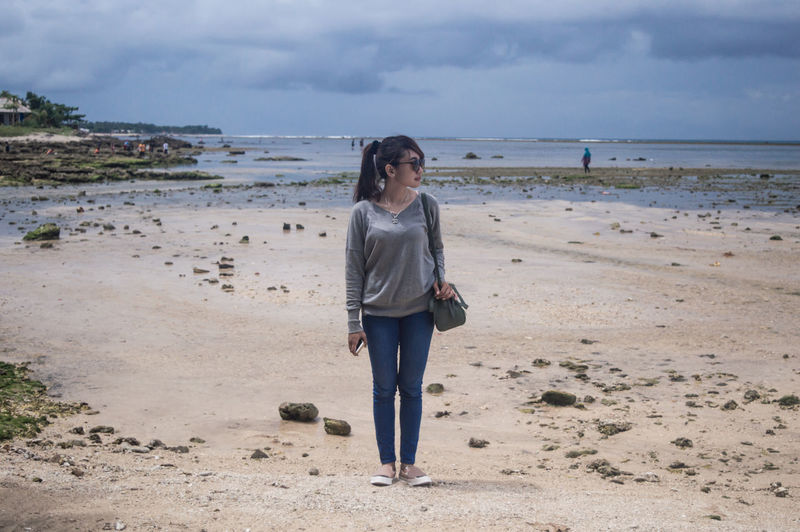 Fashionable Young Woman Standing On Beach