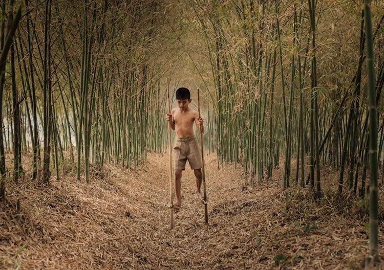 Shirtless boy walking on stilts in forest