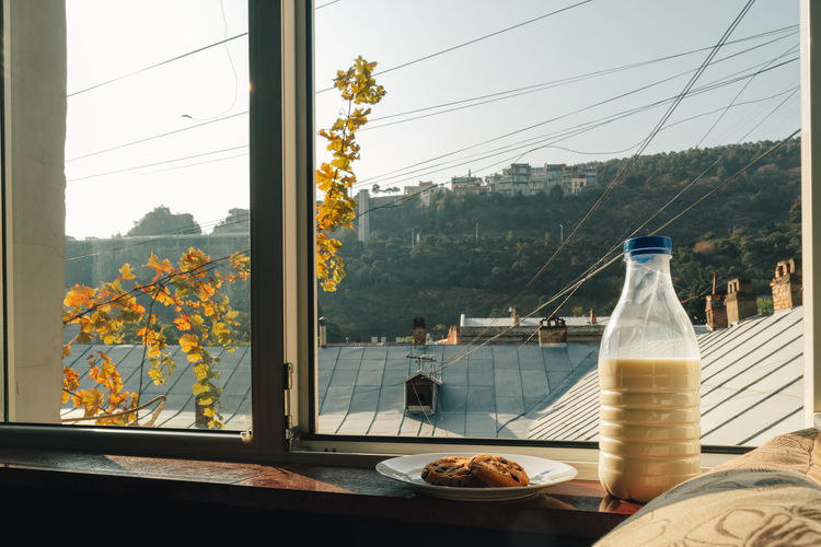 Panoramic shot of glass on table by window against clear sky