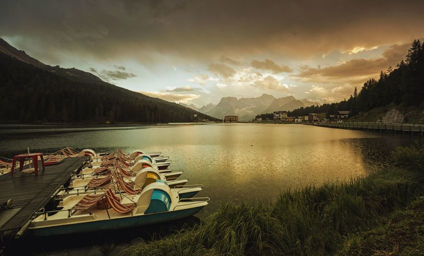 Paddleboats Moored On Lake Misurina Against Cloudy Sky During Sunset