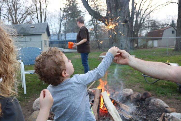 Togetherness Barbecue Childhood Family Child Burning Flame Human Body Part Mid Adult Outdoors Leisure Activity Father Real People Lifestyles Mid Adult Men Front Or Back Yard Camping Girls Barbecue Grill Boys Sparklers Live For The Story