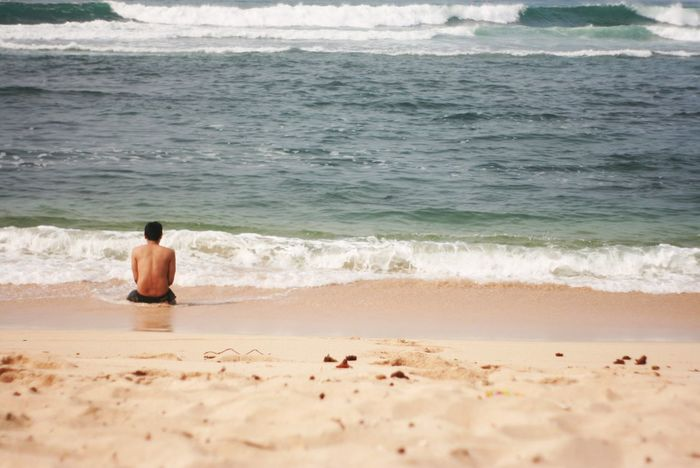 Rear View Of Shirtless Man Sitting On Shore Asian  Java Adult Adults Only Beach Beauty In Nature Day Horizon Over Water Men Nature One Man Only One Person Only Men Outdoors Real People Rear View Sand Sea Shirtless Sitting Solitude Water Wave Young Adult