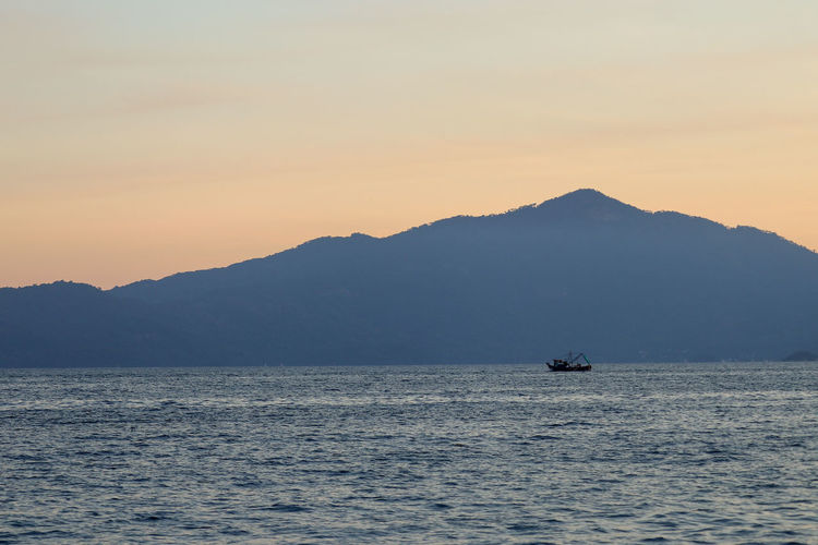 fishing boat in the sea near mountains Boat Minimalism Sea Camarao Camarones Fishing Sunset Mountain Sunset Water Silhouette Fog Sky Landscape Fishing Industry Fish Market Fishing Boat Catch Of Fish