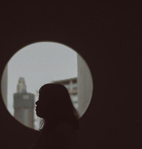 Portrait of silhouette woman seen through window