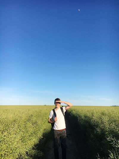 Full length of man standing on field against clear sky