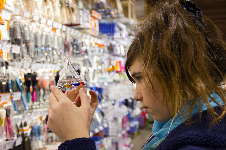 Side view of young woman looking at galileo thermometer at store