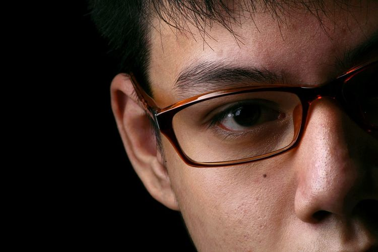 Cropped portrait of young man wearing eyeglasses against black background