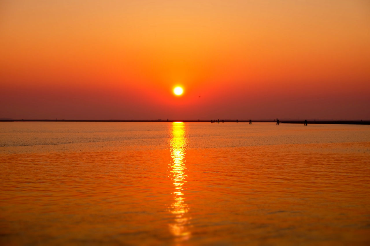 Scenic View Of Sunset At Calm Sea Against Clear Sky