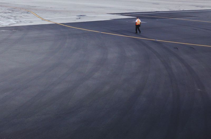 Full length of worker walking on airport runway
