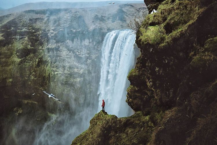 Man standing on rock by waterfall