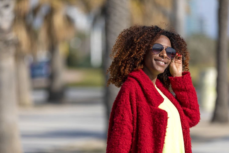 Front view of young beautiful curly woman standing on path smiling while looking camera in sunny day Smiling One Person Young Adult Happiness City Waist Up Focus On Foreground Emotion Adult Clothing Women Glasses Young Women Beautiful Woman Beauty Leisure Activity Standing Red Lifestyles Hairstyle Warm Clothing Scarf Outdoors Woman African American Curly Hair Afro Denim Happiness Happy Fun Daylight Sunlight