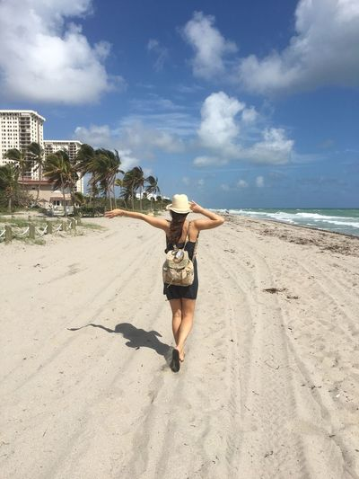 Rear view of young woman with backpack and hat walking at beach against blue sky