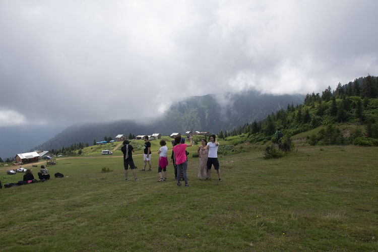Group of people on mountain range against sky