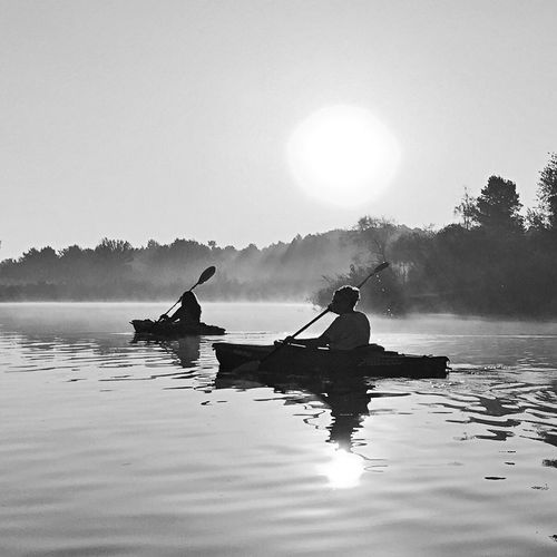 Silhouette people on boat in lake against clear sky