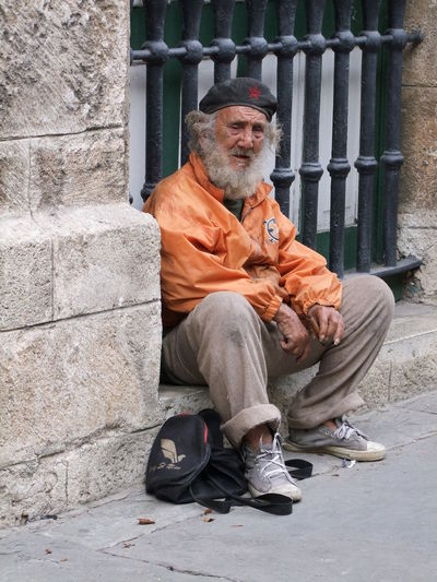 Cuban Revolunista Bearded Beret Character Composition Cuba Cuban Man Elderly Man Experienced Full Frame Havana Leisurely Lifestyles Looking At Camera Orange And Brown Outdoor Photography Portrait Relaxation Resting Revolunista Sitting Sunlight Tourism Tourist Attraction  Tourist Destination Traditional