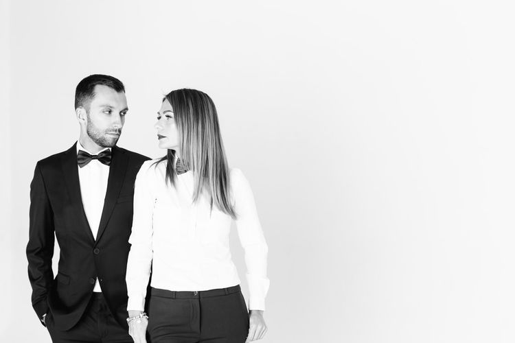 Elegant man looking at thoughtful woman against white background