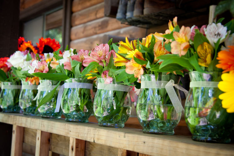 Colorful flowers in glass vases on wooden railing at shop