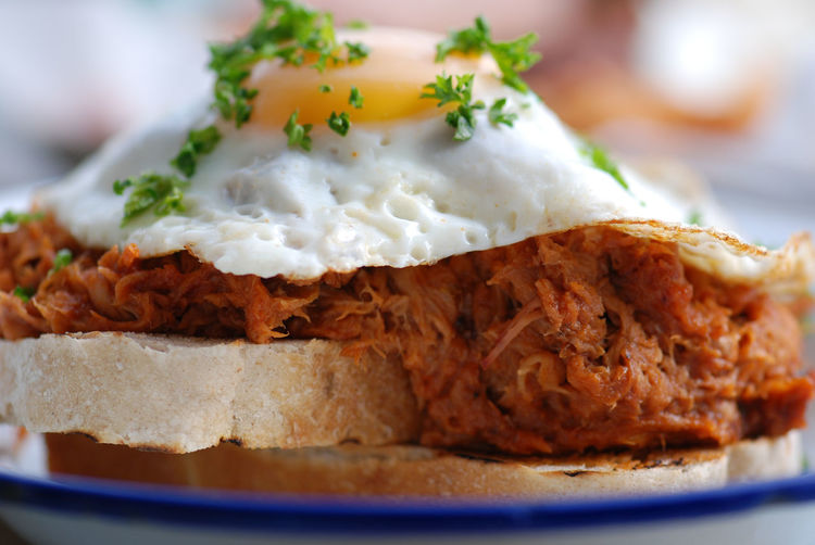 Close-Up Of Pork With Fried Egg And Bread In Plate