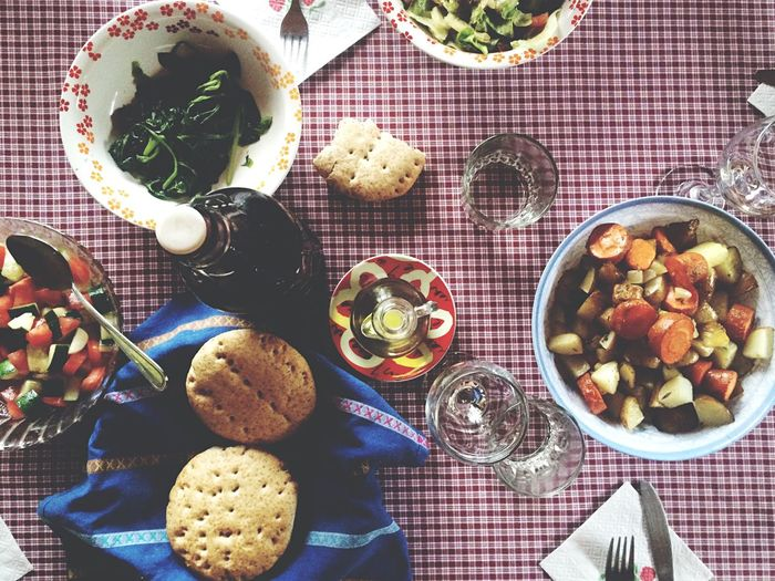 Directly above view of salad and biscuits with tablewear on checkered tablecloth