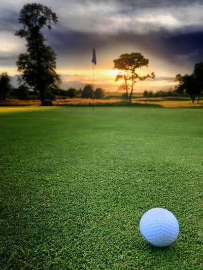 Golf ball on field against sky during sunset