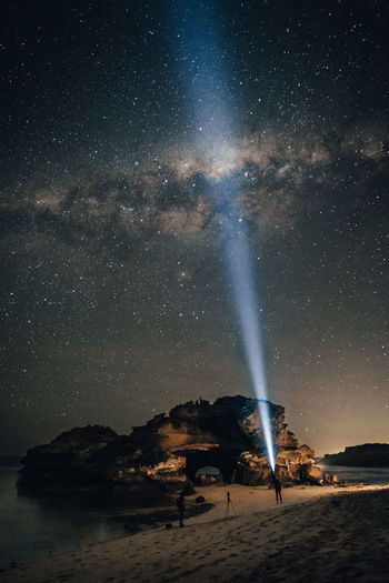 Man pointing flashlight towards stars in sky