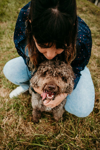 Portrait of woman with dog on field