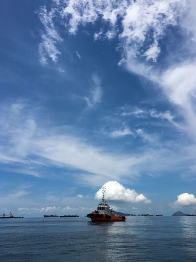 Boat Sailing In Sea Against Cloudy Sky