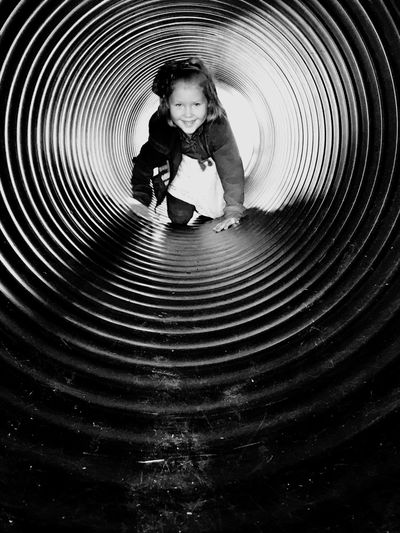 Portrait of girl crawling in pipe