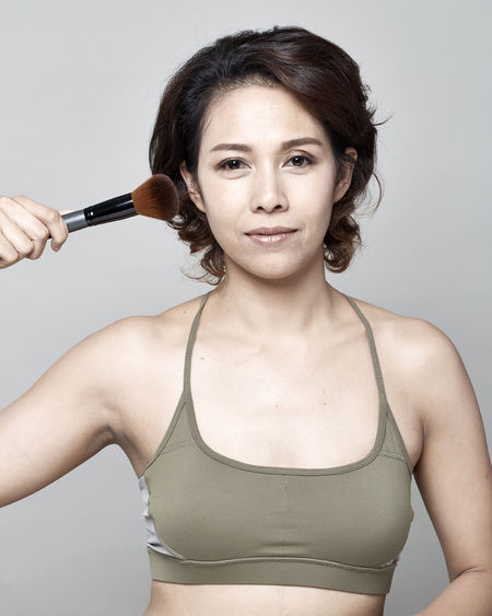 Portrait Of Woman Applying Make-Up With Brush Against Gray Background