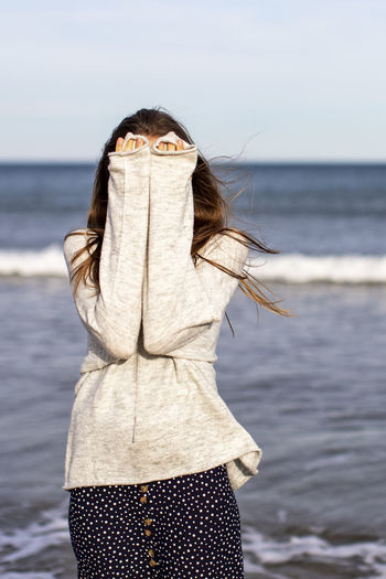 Portrait of woman standing at beach against sky
