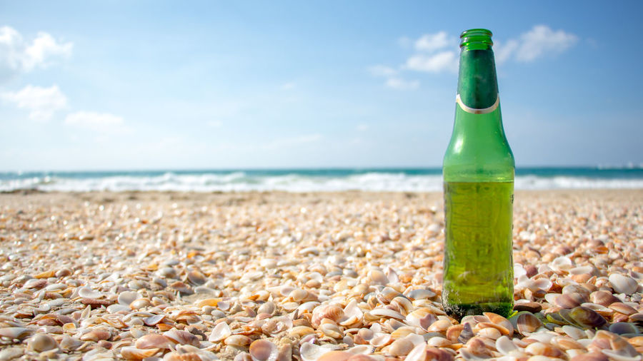 Close-up of bottle on seashells at beach against sky