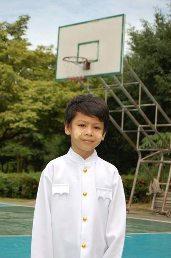 Portrait of cute boy wearing traditional clothing while standing on court against basketball hoop