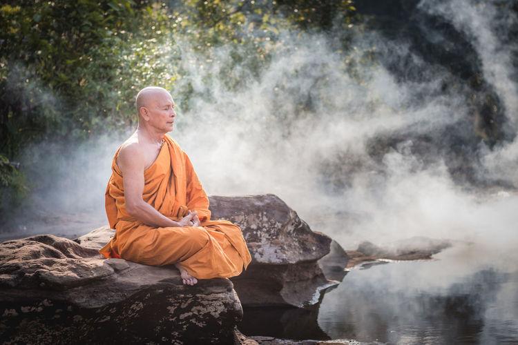 Man Meditating On Rocks