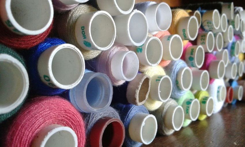 Close-up of multi colored spools on table