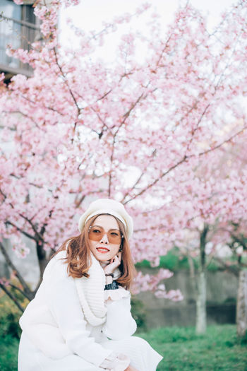 Portrait of woman standing by pink cherry blossom