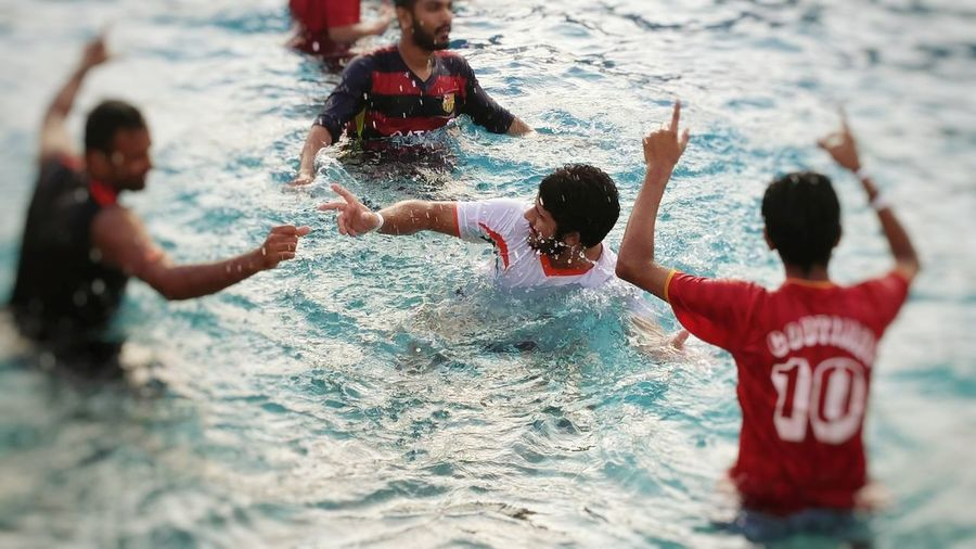 Male friends dancing in swimming pool at water park