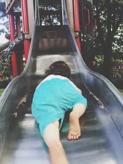 Rear view of child sliding at park