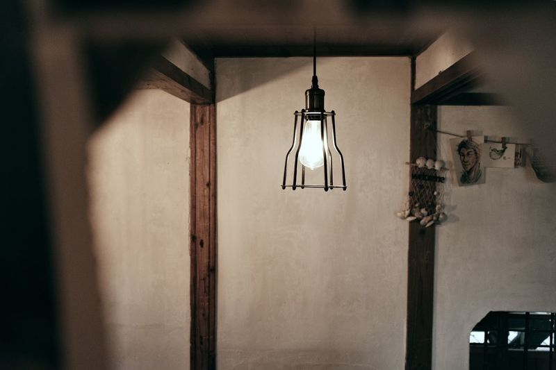 Close-up of illuminated lamp hanging on wall at home
