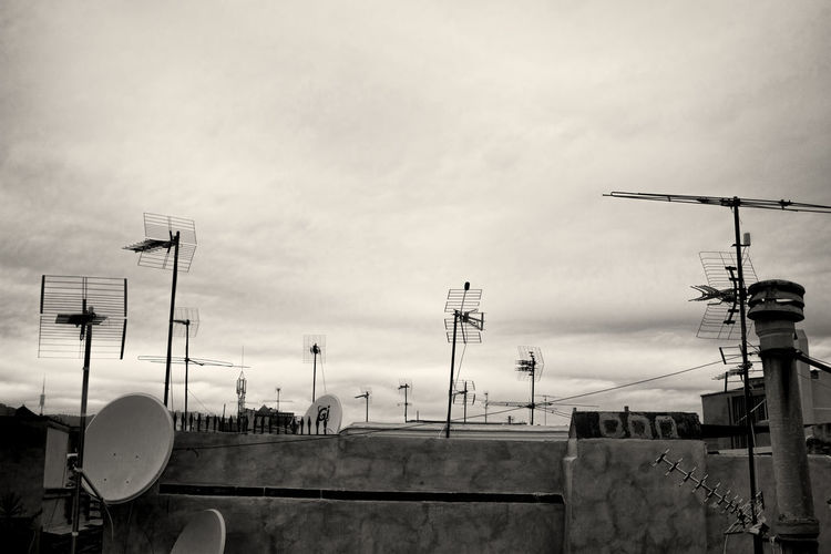 Satellite dish and antenna on rooftop against cloudy sky