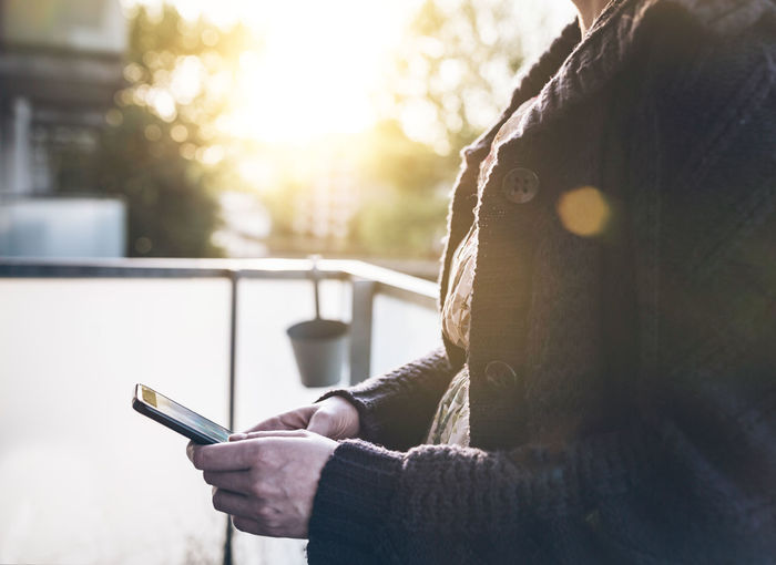 Midsection Of Woman Wearing Warm Clothing While Using Mobile Phone