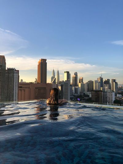 Rear view of woman in infinity pool with petronas towers in background
